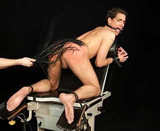 Patrik Nalup is naked, on his knees with is hot ass exposed as he is shackled to the exam chair. He is gagged too and soon feels the heavy hand of his tormentor as his lands oh his sexy ass.
